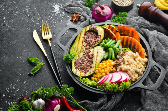 Vegan bowl: quinoa, avocado, pumpkin with beans and corn in a black bowl. Diet. Top view. Free space for text.