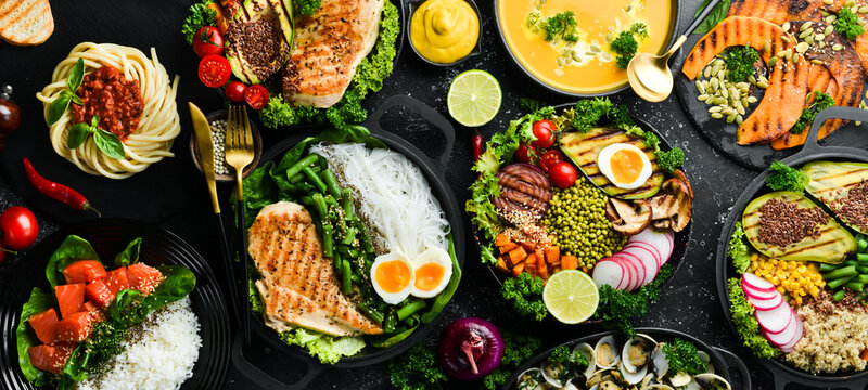 Food background: pasta, chicken, pumpkin, salad, meat, mushrooms, vegetables. On a black stone background. Top view. Free space for text.