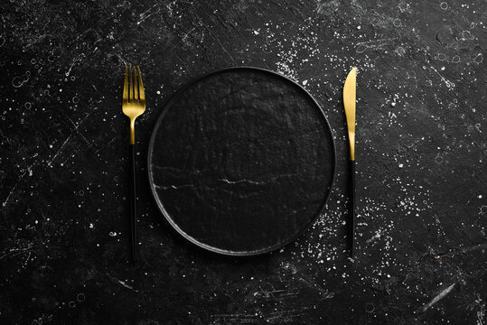 Cutlery and black plate on a black stone background. Top view. Free space for text.