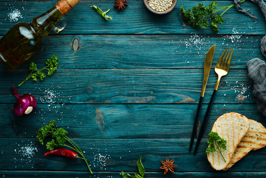 Culinary banner: Spices, vegetables and cutlery on a blue wooden background. Top view. Free space for text.