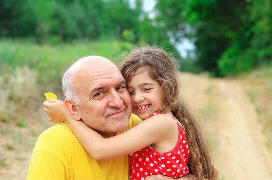 Portrait of granddad and granddaughter smiling at the park
