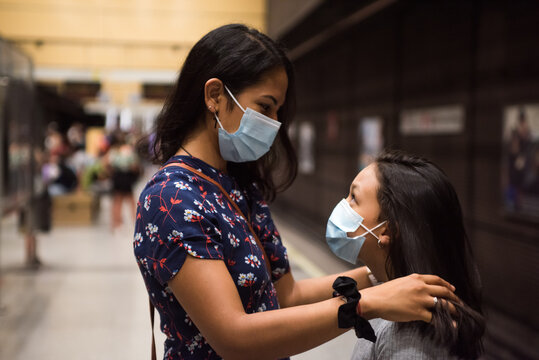 Concept of family care. Young mother care of her daughter wearing face mask during new normal on the metro station.