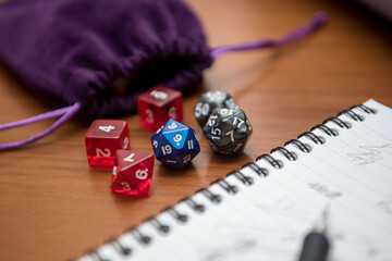 Set of pen, notebook, and dices to play role game like dungeons and dragons. Purple bag to storage the dices.