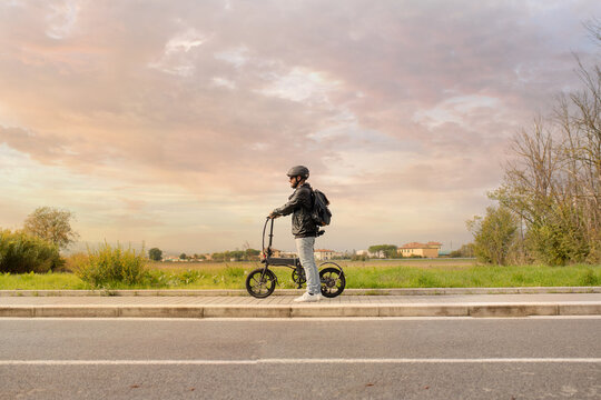 Smiling man with helmet and his electric bicycle at sunset. Commuter and new transportation concept. Green energy. Caucasian man drives his foldable e bike to go work or in leisure