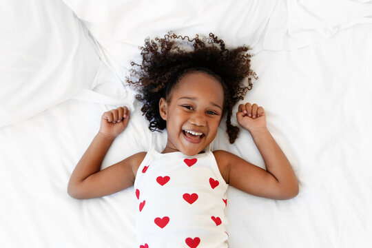 Cute little girl lying on bed smiling at camera