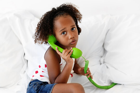 Cute young girl holding green corded phone