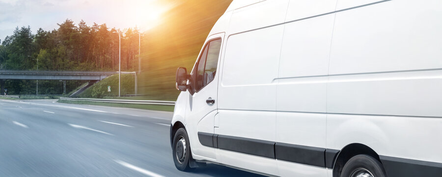 White modern delivery small shipment cargo courier van moving fast on motorway road to city urban suburb. Busines distribution and logistics express service. Mini bus driving on highway day. banner