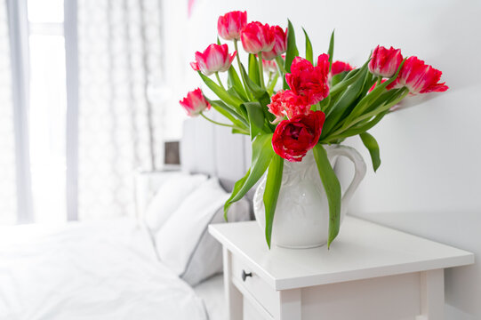 Bedroom in soft light colors..White vase with red tulips in light cozy bedroom interior. White wall, bed with white linen,