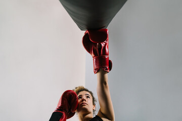 View from below of a Caucasian girl wearing red punching gloves hitting a straight punching bag at a gym