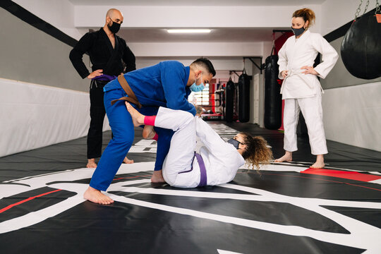 group of four martial arts partners and an instructor practicing new techniques with face masks due to the covid19 coronavirus pandemic on a gym mat