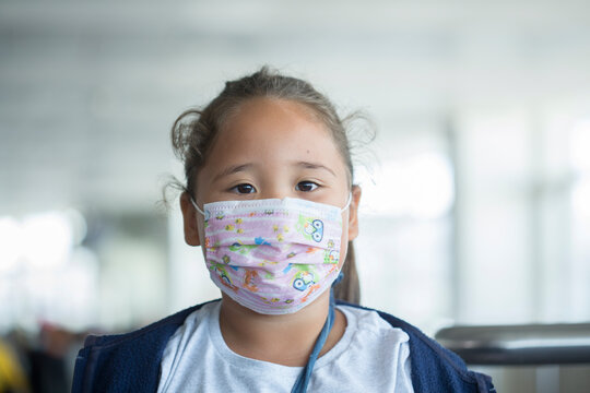 Little girl in mask sitting in the airport and airplane while covid epidemia