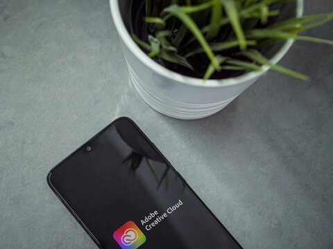 Lod, Israel - July 8, 2020: Modern minimalist office workspace with black mobile smartphone with Adobe Creative Cloud app launch screen with logo on a marble background. Close up top view flat lay.