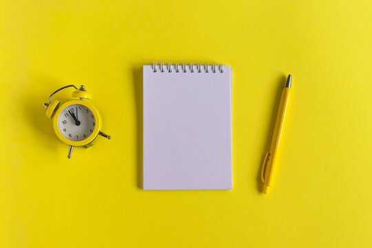Clean Notepad, clock and pen on a yellow background, spiral notebook on the table. Business, training, education. Monochrome yellow and minimalism. top view.