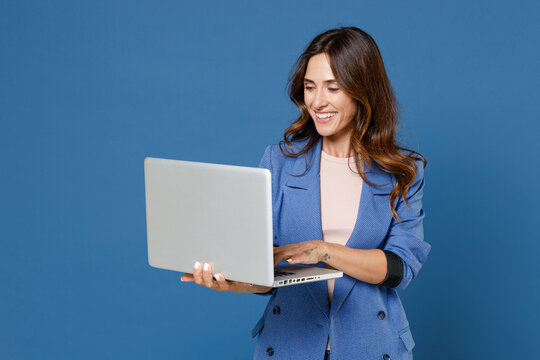 Smiling cheerful funny beautiful attractive young brunette woman 20s wearing basic casual jacket standing working on laptop pc computer isolated on bright blue colour background studio portrait.
