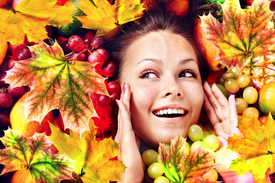Autumn leaves background with beauty face and hands of beautiful woman. Fashion dream in red fall color outside.