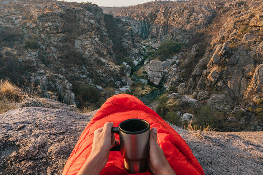 Traveler in sleeping bag with cup of coffee at the top of the mountain. Man in sleeping bag in the mountains. Mountains of Cordoba, Argentina. Beautiful landscape