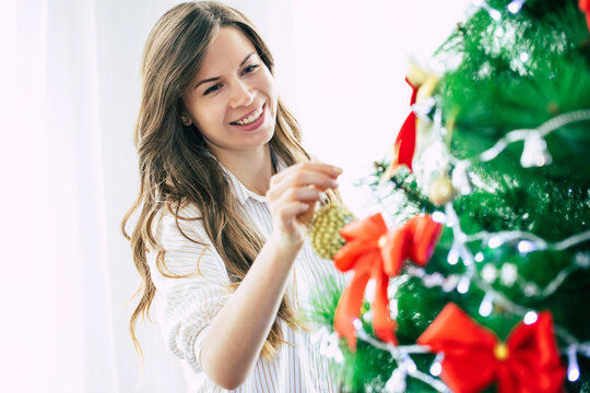 Close up photo of a beautiful happy young woman in a sweater is decorating the christmas tree at home and preparing to new year