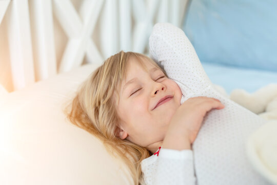 Cute adorable caucasian blond little toddler kid girl lying in bed on white pillow. Adorable sweet happy smiling child stretching wake up early morning for kindergarten or school. Childhood concept
