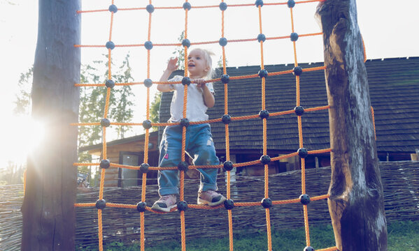Cute blond caucasian kid is climbing up the net at playground outside, rustic background, sun shines.