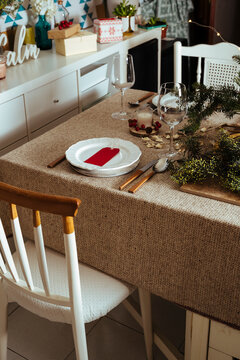 Homely christmas table setting, with pine branches rustic tablecloth in the living room of home. European style with Christmas lights.