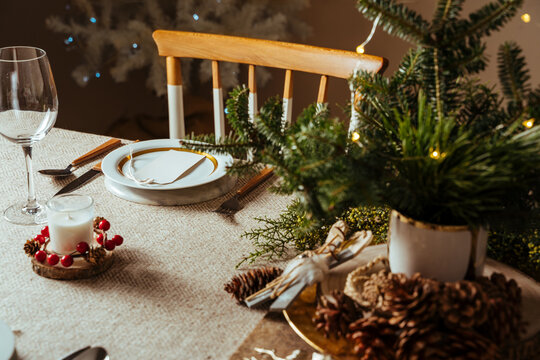 Homely christmas table setting, decorated with pine branches and rustic tablecloth in the living room of home tree lit background