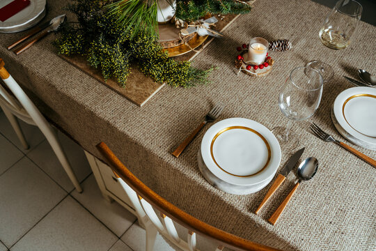 Holiday Gold place setting,  Christmas table with ornaments and natural pine branch on the livingroom home
