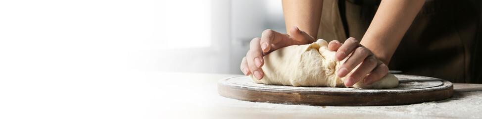 Baker kneading dough at table, closeup. Banner design with space for text