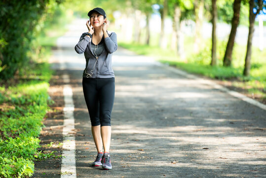 Healthy woman jogging run and workout on road outdoor. Asian runner people exercise gym with fitness session, nature park background.
