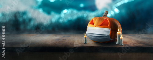 concept - Jack O 'Lantern on wooden table on spooky Halloween night with mask and glowing eyes during coronavirus pandemic COVID-19