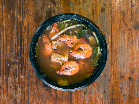 Sinigang na Hipon is a type of Filipino sour tamarind soup. Top view, on a wood table.