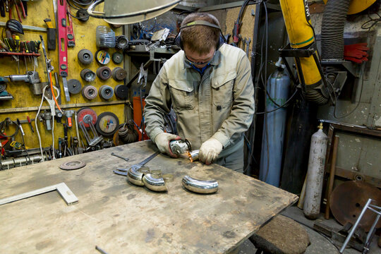 Fitting a polished stainless steel elbow with a sander