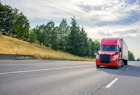 Red big rig semi truck with black grille transporting cargo in semi trailer driving on the straight wide highway road with trees on the hillside