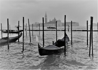 Venice, Italy, December 28, 2018 evocative black and white image of a gondola moored with San Giorgio island in the background