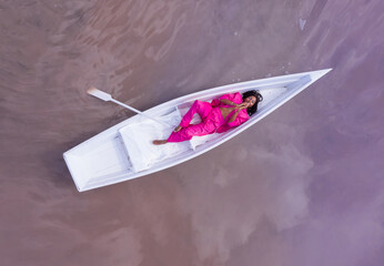 Amazing dream fairy fabulous fantasy style composition black woman in pink suit lying white boat and looking up camera. Aerial drone artistic creative conceptual imagination subconscious psychotherapy
