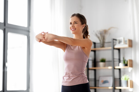 sport, fitness and healthy lifestyle concept - smiling young woman stretching arms at home
