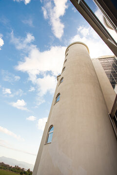 Round residential tower with windows on a background of blue sky with clouds
