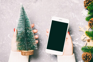 Wall Mural - Top view of a woman holding a phone in her hand on cement New Year background made of fir tree and festive decorations. Christmas holiday concept. Mockup