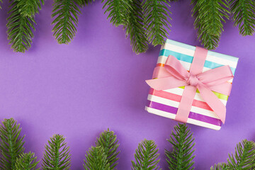 Wall Mural - Top view of gift box and fir tree branches on colorful background. Merry Christmas concept with empty space for your design