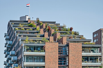 Rotterdam, The Netherlands, September 19, 2020: modern brick residential building at Kop van Zuid neighbourhood with a stepped upper section with terraces