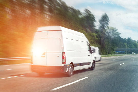 White modern delivery small shipment cargo courier van moving fast on motorway road to city urban suburb. Business distribution and logistics express service. Mini bus driving on highway on sunny day
