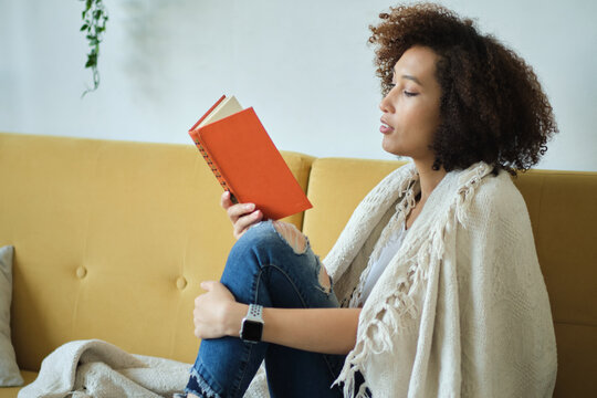 Beautiful young African American woman reading a book lying comfortably on her back on a couch in the living room in her jeans