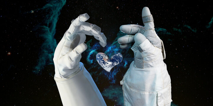 Earth heart in astronaut hands in space background, among stars and galaxies, World environment day and give love to our world concept. Elements of this image furnished by NASA.
