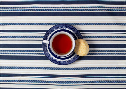 A cup of tea with a cookie in the center on a striped tablecloth; cenital plane