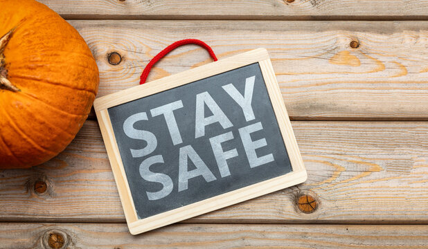 Stay safe message and thanksgiving pumpkin against wooden background. COVID 19 days