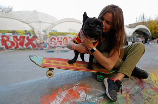 A French Bulldog named Nord Boss poses for a picture with his owner Natasha at a skatepark in Moscow