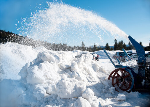 Snow plough blowing piles of snow. Rotary snow blower prepares new parking lots for happy winter tourists and cross country skiers in Jizerka settlement in Jizera mountains (Czech: Jizerske hory)