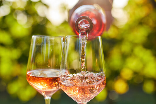 Pouring rose wine into glasses from a bottle