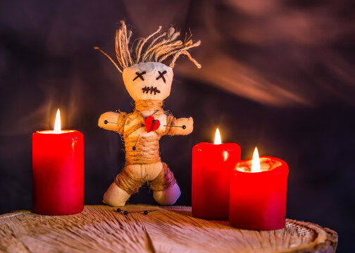 A voodoo doll stands on a wooden table between burning candles.