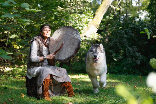 Shaman woman with an Alaskan Malamute dog in the sunny forest