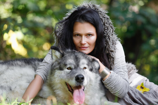 Portrait of a pretty woman with an Alaskan Malamute dog outdoors
